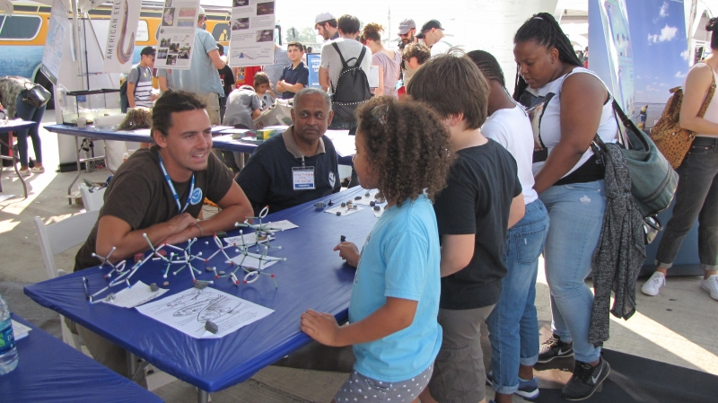 Children speaking with NOAA presenters at a table.