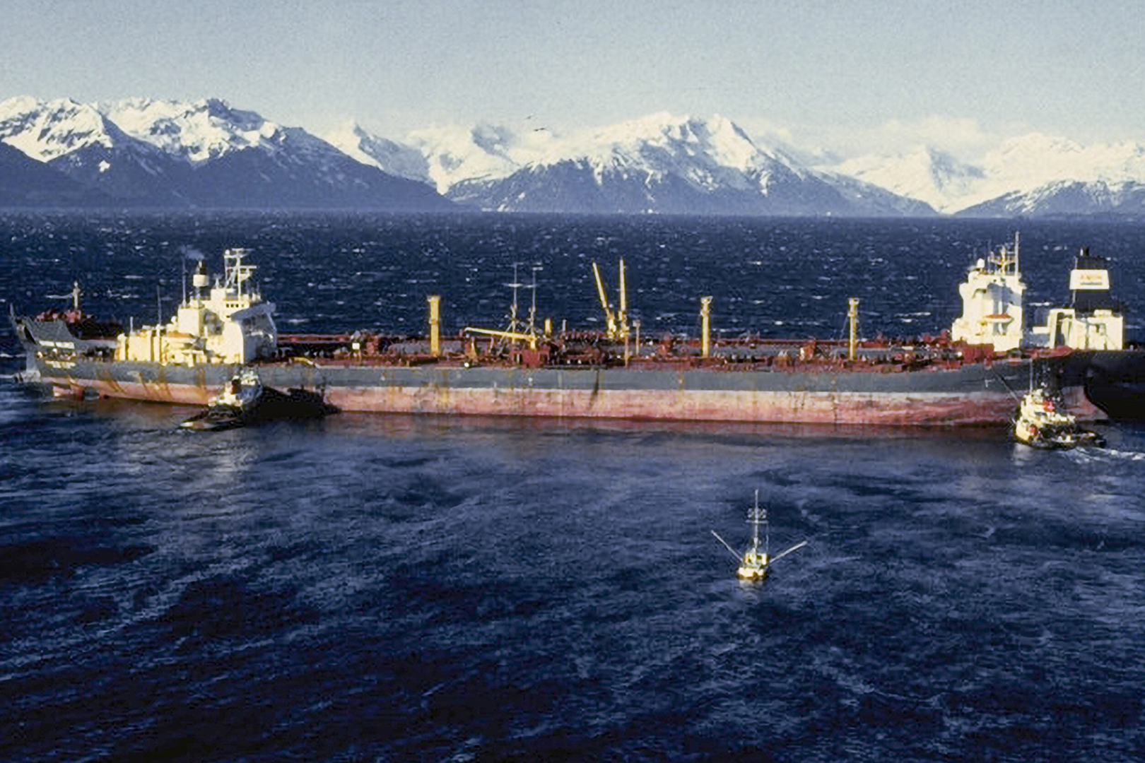 A vessel in water with snowy mountains in the background.