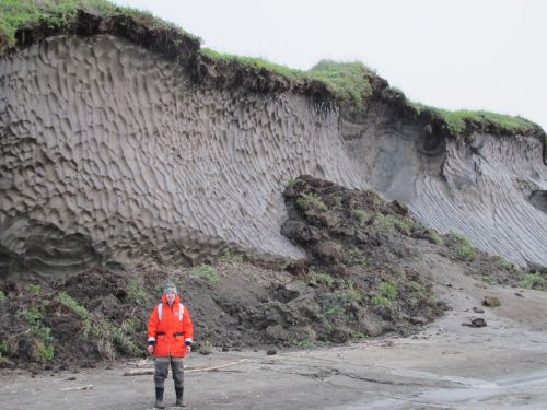 A woman with a wall of exposed permafrost behind her.