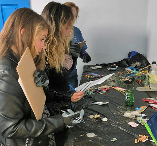 People looking at pieces of trash.