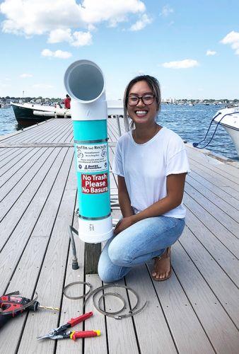 "Woman posing next to a ""bin"" on a pier."