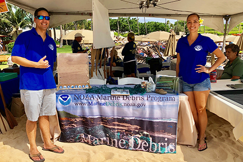 Man and woman standing at an outdoors exhibit table.