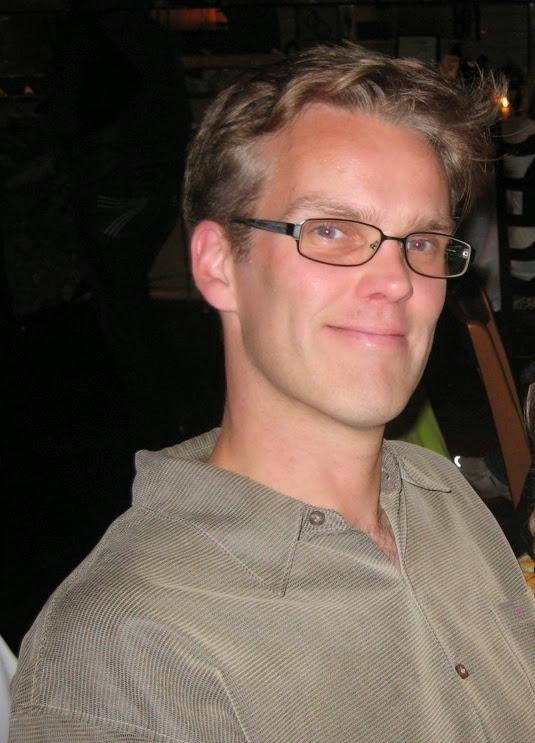 Man in a tan shirt posing for photo.