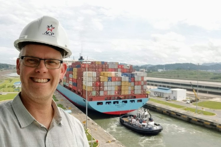 A man in a hard hat with a container ship in a canal lock behind him.