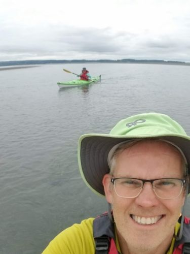A man taking a selfie from a kayak with another kayaker behind him.