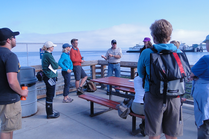 A group of people standing outside in front of a body of water with vessel traffic.