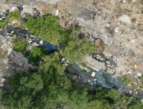 Aerial view from uncrewed aircraft, showing oiling in a creek bed.
