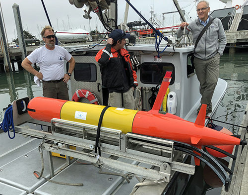 three men in a boat looking at a Long-Range Autonomous Underwater Vehicle on the deck.