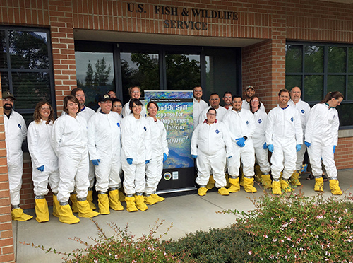 Group in white Hazmat suits posing for photo.