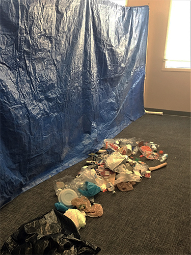 A pile of trash in front of a hanging, blue tarp.