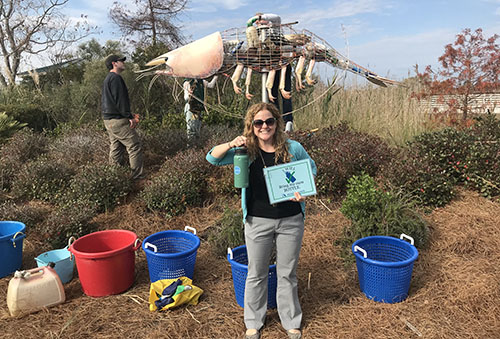 Woman outdoors with sculpture and marine debris.