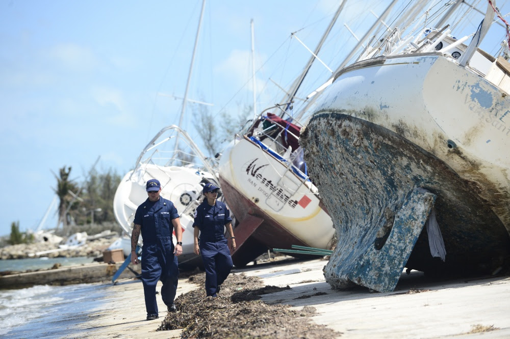 Two people walk by a vessel, tipped on its side on land.
