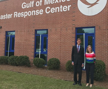 "Two people in front of a building that reads ""Gulf of Mexico Disaster Response Center."""