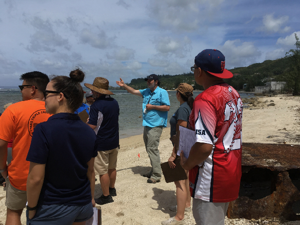 A group of people listening to an instructor on a beach.