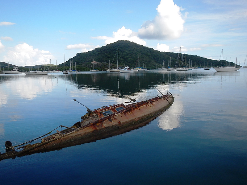 A derelict vessel that is almost completely submerged.