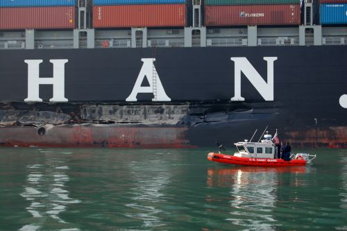 A small U.S. Coast Guard vessel in front of a gash in a container ship.