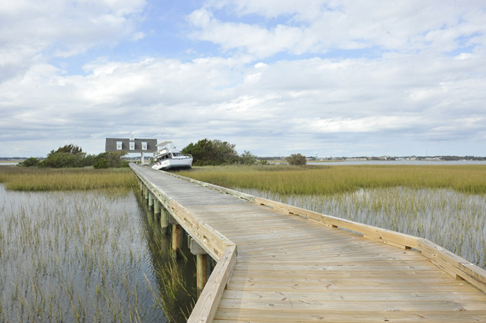 A boardwalk in the foreground extending toward a displaced vessel on a grassy shoreline.