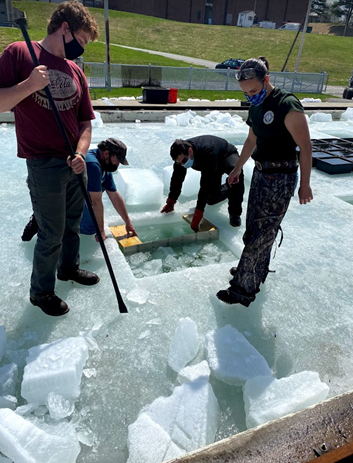 People standing on ice with a square cut into the ice.