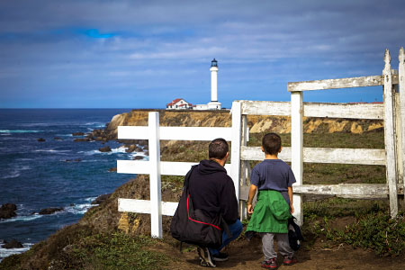 Two people looking at a lighthouse.