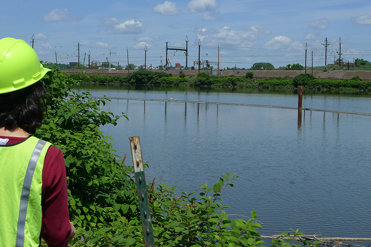 A person in a hard hat looking across a river at an industrial shoreline.