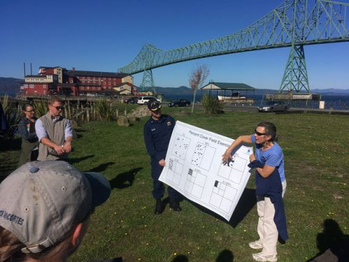 Two instructors hold up a diagram to explain to several students the percent cover of oil. Bridge in background.