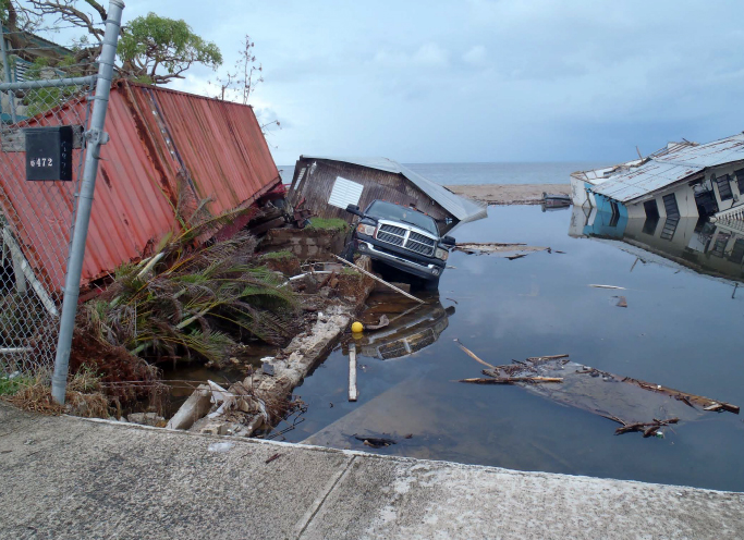 Shipping container tipped over at the water's edge, car in water, partially sunken buildings.