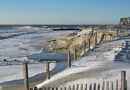 Snow on beach; fences along beach.