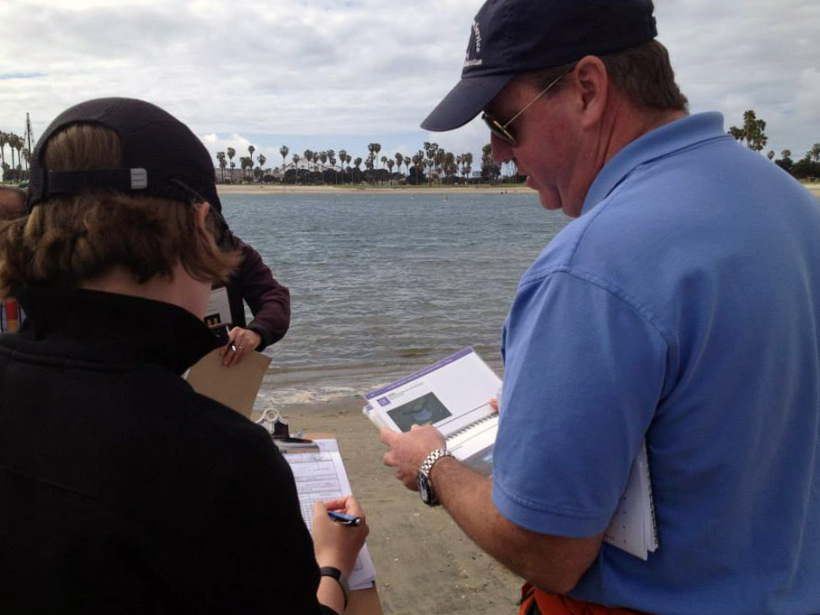 Two people on a shoreline looking at clipboards.