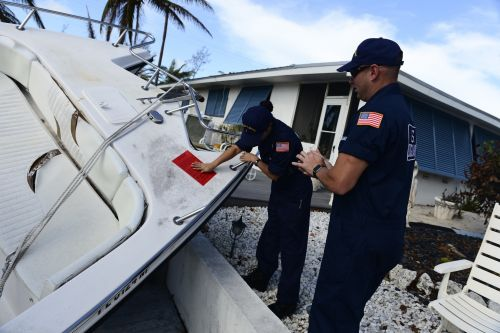 Woman placing a red tag on a vessel.