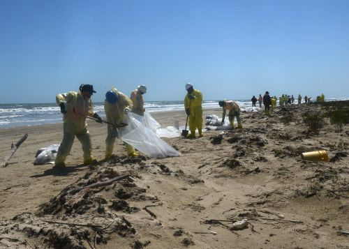 photo of people removing oil-contaminated sand from beach.
