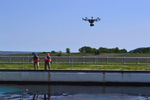 Two people at a pool's edge with oil floating on water as drone flies above.