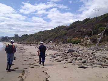 Two men walking along the beach.