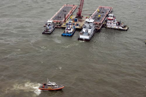 Photo of tugs and barge in water.