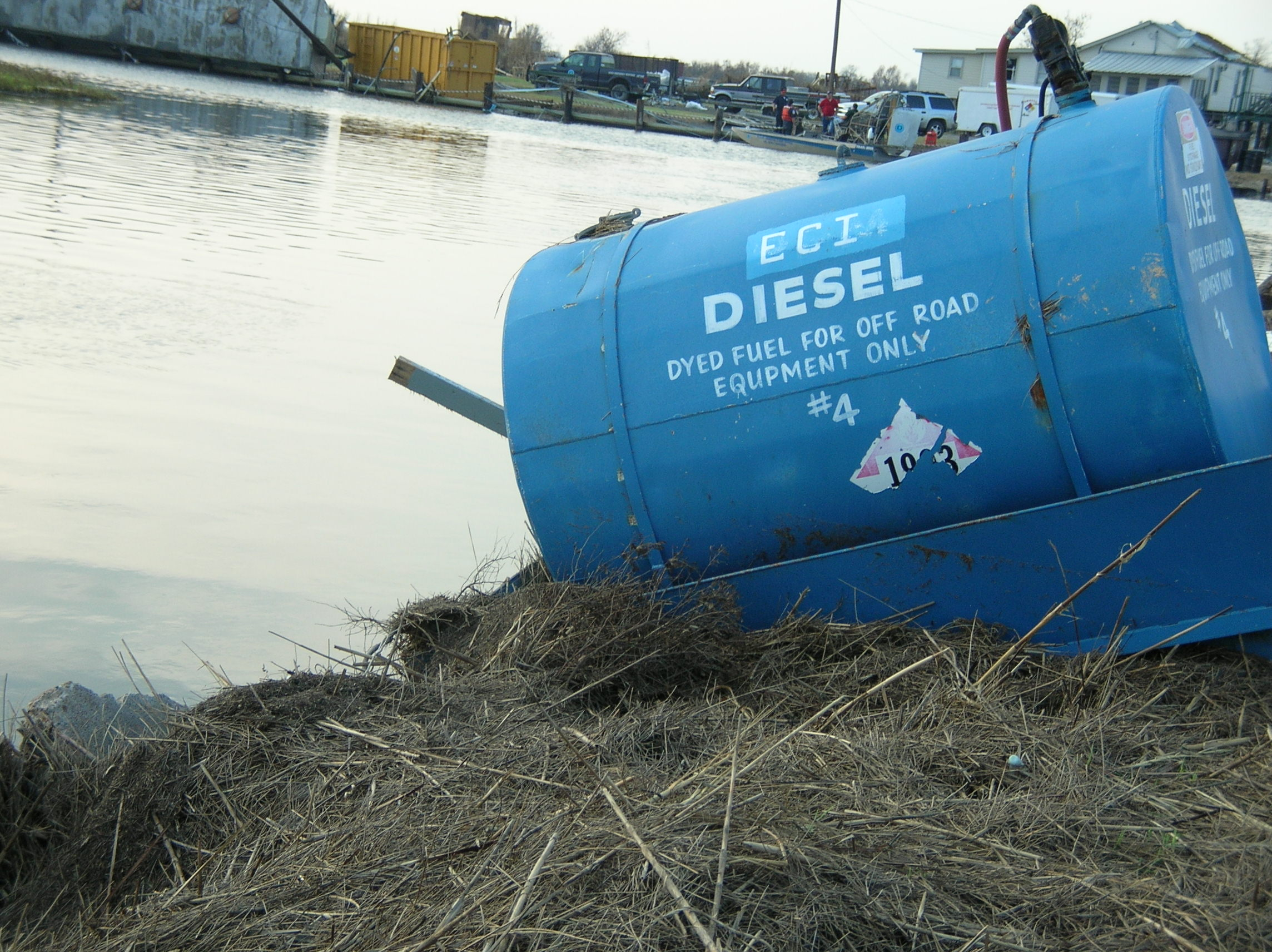 Diesel container on an embankment next to water.