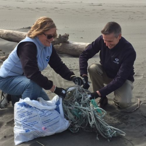 Woman and man on a beach gathering trash into a bag.