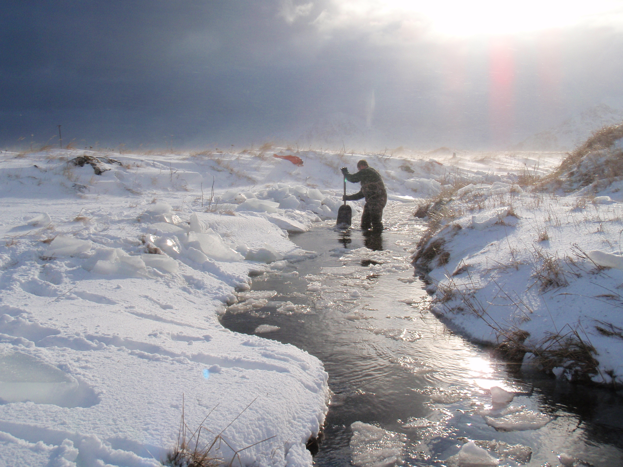Two people sampling in a stream after the Adak oil spill.