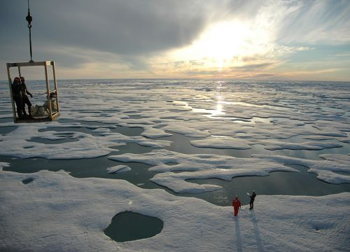 Frozen seascape with two individuals standing on ice.