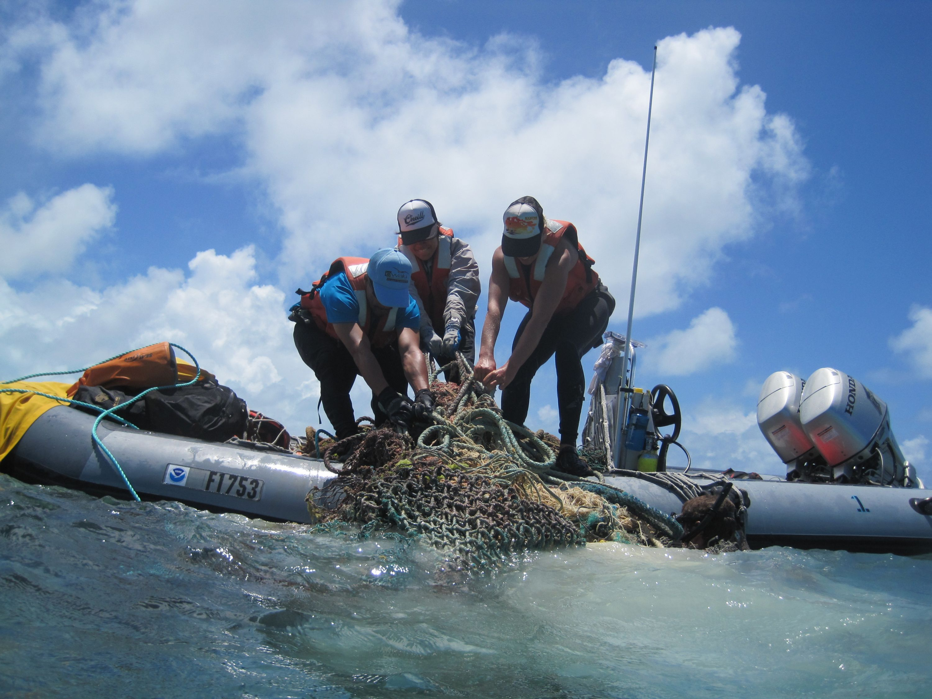 Image of scientists pulling discarded nets onto their boat.