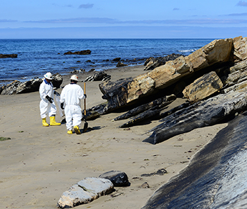 Two people dressed in cleanup suits on a beach with oiled rocks.