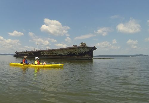 Skeleton of an old vessel in water with a yellow kayak nearby.