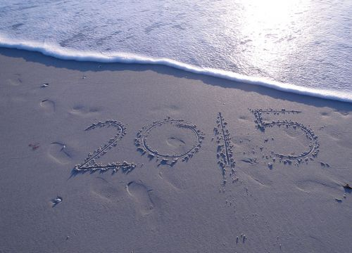 2015 written on a sandy beach with an approaching wave.