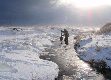 Man breaks the ice to prepare a stream for sampling on Adak Island.