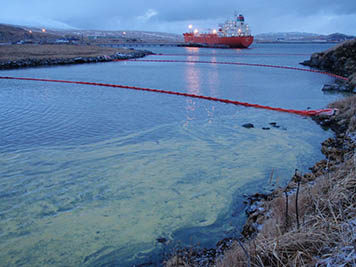 View of spilled oil and boom from the Adak Small Boat Harbor into Sweeper Cove.