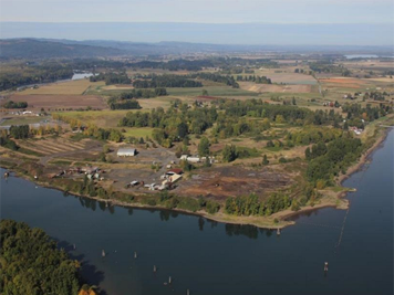 Aerial view of dirt fields and buildings along a river bend.