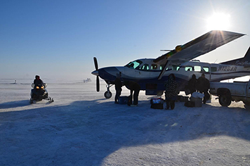 People load a propeller plane while a person approaches on snowmobile.