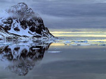 Mountain surrounded by water with floating ice in Arctic Circle.