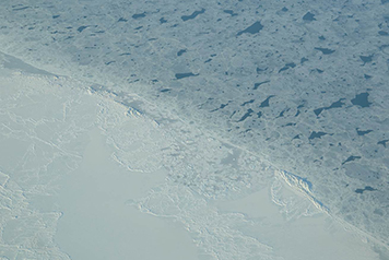 Patches of newly formed ice are visible in the open water of the Chukchi sea.
