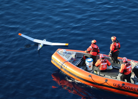People in a boat next to a small unmanned plane in the water.