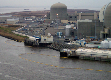 Yellow containment boom floats on a river next to a nuclear power plant.