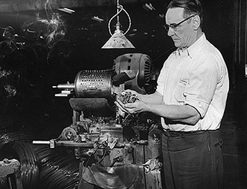 Atlas Tack Corporation worker holding metal hardware produced in the factory.